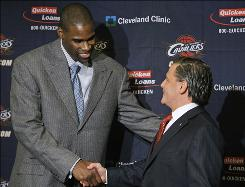Antawn Jamison, left, shakes hands with owner Dan Gilbert before a news conference Thursday. The best team in the league filled its last glaring hole when general manager Danny Ferry acquired Jamison Wednesday in a three-team trade with Washington and Los Angeles. Jamison's ability to shoot from the perimeter should create more space inside for Shaquille O'Neal and LeBron James.