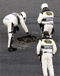 NASCAR officials examine the pothole that developed during Sunday's Daytona 500.