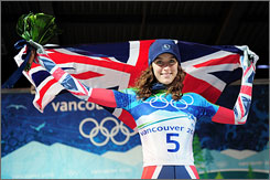 Amy Williams raises the flag of Great Britain after winning a gold medal in women's skeleton.