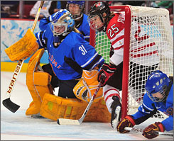 Finnish goalie Noora Raty keeps her eye on the puck while Canada's Tessa Bonhomme ends up inside the net.