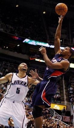 Hawks guard Joe Johnson puts a shot over the Jazz forward Carlos Boozer during the first half. Johnson led the way for the Hawks scoring 28 points.