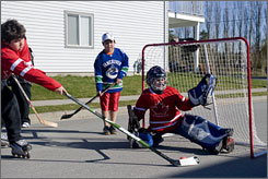 Children from Musqueam Nation play hockey on a local street.