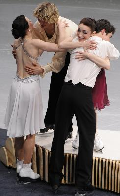 Tessa Virtue and Scott Moir of Canada (foreground) and Meryl Davis and Charlie White of the United States (on medals stand) congratulate each other before the ice dancing medals ceremony Monday. Virtue and Moir won the gold medal and Davis and White won silver.