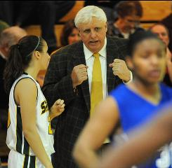 Jim Justice, owner of the Greenbrier Resort in West Virginia and coach of the girls basketball team at Greenbrier East High School, talks to Kayla Whited during a timeout in a game against Capital High.