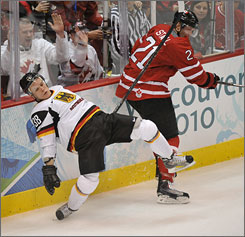 Germany's Jakub Ficenec gets knocked to the ice by Canada's Eric Staal in Tuesday's game, which Canada won 8-2 to reach the quarterfinals.