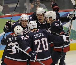 Zach Parise (9), who scored both goals, celebrates with his teammates Wednesday after the USA defeated Switzerland 2-0 in an Olympic hockey quarterfinal.