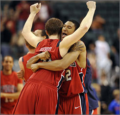 Richmond's Dan Geriot, near, and teammate Justin Harper celebrate the Spiders' victory over Florida on Dec. 19.