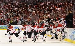 Canada's women's hockey team rushes the ice after defeating Team USA 2-0 to win the gold medal Thursday.