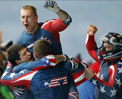 Curtis Tomasevicz leaps into the arms of teammates Justin Olsen and Steve Mesler after they joined driver Steven Holcomb to capture the gold medal in four-man bobsled Saturday at the Winter Olympics in Whistler. It's the USA's first gold in the event since 1948.