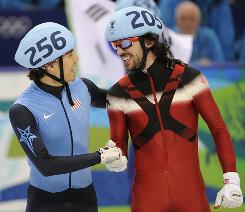 USA's Apolo Anton Ohno congratulates Canada's Charles Hamelin following Canada's win in the men's 5,000-meter team relay. Ohno and the USA got bronze for Ohno's eighth Olympic medal. He was disqualified in the 500-meter race, which Hamelin also won.