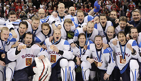 Finland's players celebrate with their bronze medals after rallying to beat Slovakia on Saturday night. With the victory, the Finns have medaled in four of the five Winter Olympics since the NHL began allowing its players to participate.