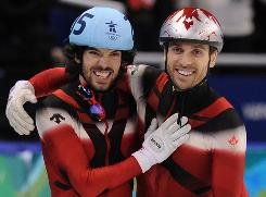 Charles Hamelin, left, and Francois-Louis Tremblay celebrate their gold-medal finish in the men's 5,000-meter short-track relay final at the Pacific Coliseum in Vancouver on Friday. Canada ended up with 14 gold medals overall, the best ever in the Winter Games.