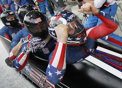 From right, USA-1's Steven Holcomb, Justin Olsen, Steve Mesler and Curtis Tomasevicz celebrate their victory in the four-man bobsled at the Whistler Sliding Centre. It was the USA's first gold medal in the event since 1948.