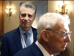 Pittsburgh Steelers team president Art Rooney II, left, looks on as his father, chairman Dan Rooney talks with reporters after an NFL owners meeting in 2008. Rooney II says he is not tempted to splurge during the uncapped free agency period.