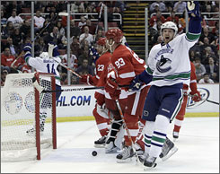 Canucks center Henrik Sedin, right, celebrates a goal by teammate Alexandre Burrows, far left, during the first period of Vancouver's 6-3 win over Detroit.