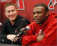 Outfielder Justin Upton, right, talks about his new six-year contract with Arizona during a news conference as vice president and general manager Josh Byrnes looks on.