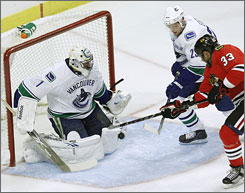 Canucks goalie Roberto Luongo, stopping Dustin Byfuglien's shot for the Blackhawks, was removed during Chicago's first-period goal blitz.