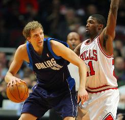 Dallas Mavericks forward Dirk Nowitzki, left, is guarded by Chicago Bulls forward Hakim Warrick during the first half at the United Center. Nowitzki scored 27 points as the Mavericks defeated the Bulls 122-116 Saturday night.