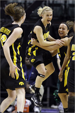 Iowa's Kamille Wahlin, center, jumps into the arms of teammate Trisha Nesbitt, right, as Morgan Johnson looks on after the Hawkeyes' 59-54 win over Michigan State in the Big Ten semifinals.