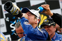Kurt Busch celebrates with champagne as he is doused with his sponsor's product in victory lane at Atlanta Motor Speedway.