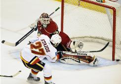 Calgary Flames defenseman Steve Staios hits the goal post as Minnesota Wild goalie Niklas Backstrom makes a move for the save during the third period.