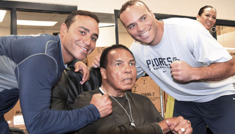 Boxing great Muhammad Ali, poses with brothers Jerry Hairston Jr., left, and  Scott Hairston at the San Diego Padres spring training baseball facility.