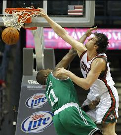 Milwaukee center Andrew Bogut dunks the ball over Boston's Glen Davis in the first half. Bogut finished with 25 points and 17 rebounds.