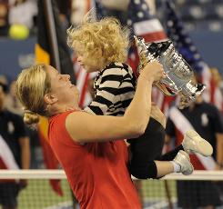 Kim Clijsters of Belgium juggles daughter Jada and the championship trophy after winning the U.S. Open in September. Clijsters returned last year from a nearly two-year retirement, and her schedule is a challenge now.