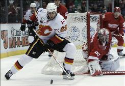 The Flames' Eric Nystrom retrieves a rebound from a blocked shot by Red Wings goalie Jimmy Howard in the first period Tuesday night in Detroit. Howard recorded 28 saves and allowed three goals. The Red Wings pulled him with less than a minute left in the game.