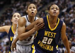 Connecticut forward Maya Moore, center, fights for position against West Virginia center Asya Bussie, right, and guard Liz Repella during the first half.