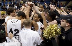 Oakland's basketball team celebrates after clinching the school's second NCAA tournament berth and first in five years after its Summit League championship-game win over IUPUI.