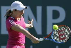 Justine Henin of Belgium chips a backhand in her first-round victory against Magdalena Rybarikova of Slovakia on Wednesday in the BNP Paribas Open in Indian Wells, Calif.