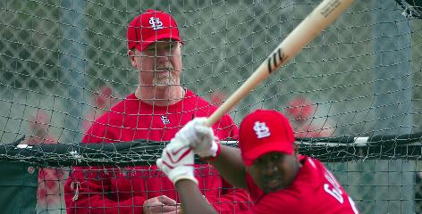 The new job for the Cardinals' Mark McGwire, shown watching second baseman Ruben Gotay take his cuts, comes with scrutiny over his past use of performance-enhancing drugs.