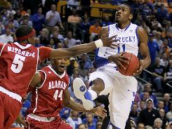 Kentucky's John Wall drives to the hoop as two Alabama defenders close in during the second-ranked Wildcats' victory in the quarterfinals of the SEC tournament in Nashville.