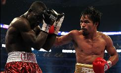 Manny Pacquiao, throwing a right at Joshua Clottey during their welterweight title fight at Cowboys Stadium, won by unanimous decision.