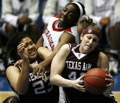 Texas A&M forward Kelsey Assarian, right, grabs a rebound from teammate Danielle Adams as Nebraska's Catheryn Redmon tries to intervene during their Big 12 semifinal matchup in Kansas City, Mo. Texas A&M won the game to hand Nebraska its first loss of the season.