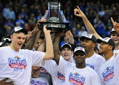 Kansas players celebrate with the championship trophy after beating Kansas State to win the Big 12 conference tournament and earn the No. 1 overall seed in the NCAA tournament.