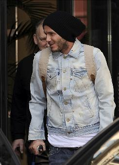 David Beckham of the Los Angeles Galaxy leans on crutches as he leaves his hotel Monday in Milan. Chelsea manager Carlo Ancelotti insisted Monday that the former England captain can recover from the injury that wrecked his World Cup dream. Beckham, 34, ruptured his Achilles' tendon during AC Milan's victory against Chievo Verona on Sunday and has flown to Finland for surgery, which is expected to keep him out of action five to eight months.