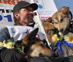 Lance Mackey holds two of his lead dogs, Rev and Maple, after winning his fourth straight Iditarod Trail Sled Dog Race in Nome, Alaska. Mackey finished with the second-fastest time in the race's history.