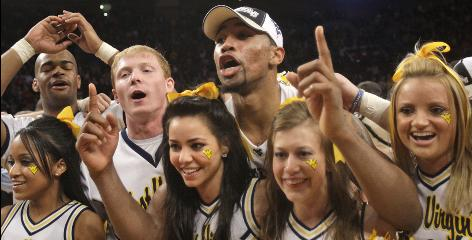 West Virginia forward Da'Sean Butler celebrates with cheerleaders after the Mountaineers won the Big East title 60-58 over Georgetown. Butler scored 20 points and the game-winning shot.