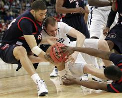 Robert Morris forward Dallas Green, left, battles for a loose ball with Villanova's Taylor King, center, during their first-round NCAA tournament game.
