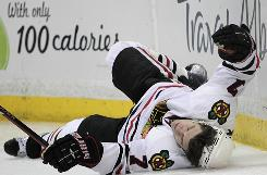 Chicago Blackhawks defenseman Brent Seabrook falls to the ice after he was checked by Anaheim Ducks defenseman James Wisniewski Wednesday night. Wisniewski was suspended for eight games.