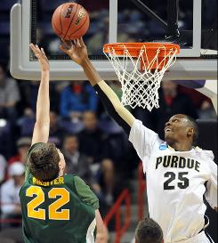 Purdue's JaJuan Johnson blocks the shot of Siena forward Ryan Rossiter during their first-round game in Spokane, Wash.