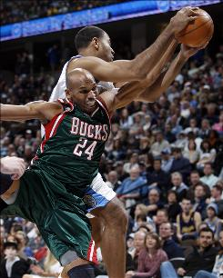 Milwaukee Bucks guard Jerry Stackhouse, front, gets tangled up while reaching for a rebound with Denver Nuggets forward Malik Allen in the first quarter of the Bucks' victory.