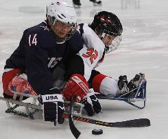 USA's Josh Pauls battles for the puck against Japan's Daisuke Uehara in the gold medal sledge hockey game at the 2010 Paralympics in Vancouver.