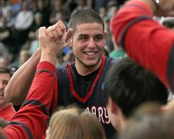 Saint Mary's Omar Samhan celebrates with fans after the Gaels stunned second-seeded Villanova 75-68 to advance to the Sweet 16.