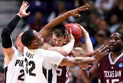 Texas A&M's Nathan Walkup is trapped by Purdue's John Hart and D.J. Byrd, behind, during their second-round battle in Spokane, Wash. Purdue's Chris Kramer made a layup in the closing seconds of overtime to propel the Boilermakers to a 63-61 victory.