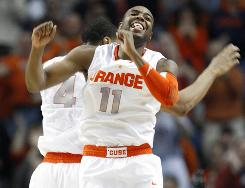 Syracuse's Scoop Jardine celebrates with teammate Wes Johnson, behind, during a break in the action of the Orange's rout of Gonzaga in a second-round NCAA tournament game in Buffalo.