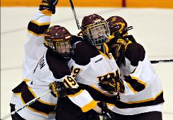 Minnesota-Duluth's Laura Fridfinnson, left, and Mariia Posa surround teammate Jessica Wong, center, after Wong scored the game-winning goal with less than a minute left in the third overtime.