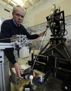 USGA senior technical director Dick Rugge works with the robotic golfer at the Indoor Test Range at the USGA Research and Test Center. The center tests 2,500 clubs and more than 1,000 types of balls each year.
